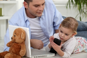bigstock-Child-playing-with-Daddy-s-cel-27436199