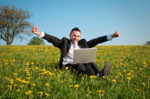man-in-field-flowers-laptop