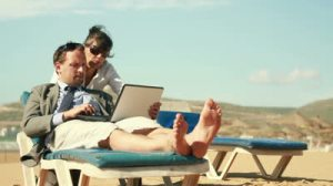 stock-footage-business-people-working-on-laptop-and-relaxing-on-the-beach